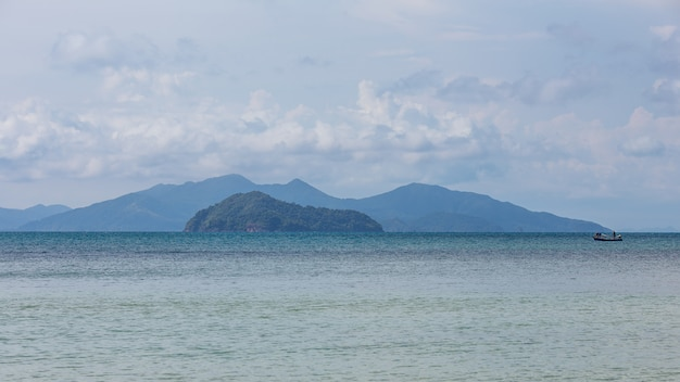 Mountain with local fisherman boat floating over the sea with bright sky at koh mak island in trat, thailand.