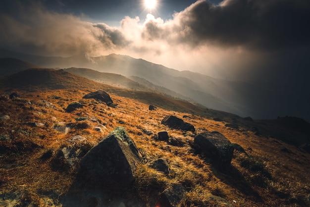 日の出の間に石と輝く太陽のある山