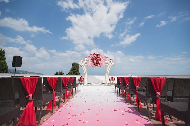 Арка красная для свадебной церемонии в море. mountain.