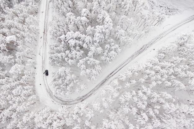雪で覆われた森の冬の谷の道路上の車。雪に覆われた森の冬の谷の道路の空中写真。高いmountain。