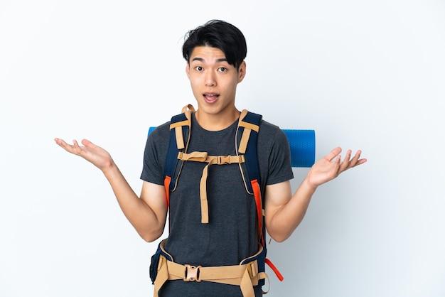 Горный китаец с изолированной на белой стене с шокированным выражением лица