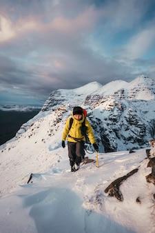 スコットランドのリアサックリッジで雪の中を登る登山家