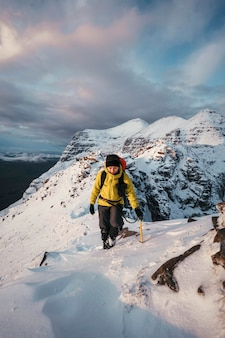 Mountaineer climbing in the snow at liathach ridge, scotland