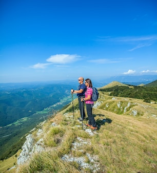 Mountaineer couple on the nanos plateau in slovenia looking at the beautiful vipava valley