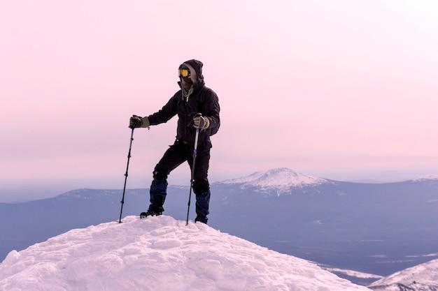 防風マスクと眼鏡をかけた登山家が山の雪の頂上に着いた