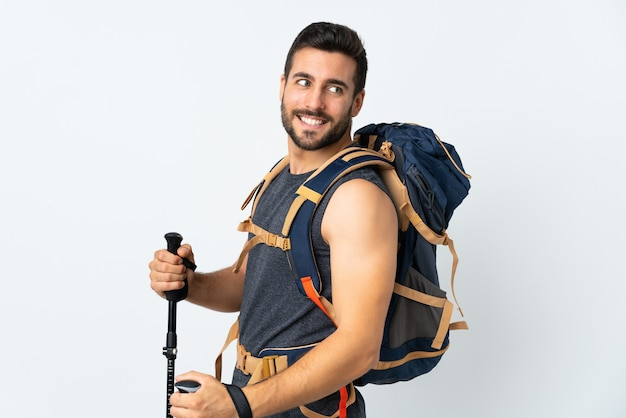 Mountaineer man with a big backpack and trekking poles