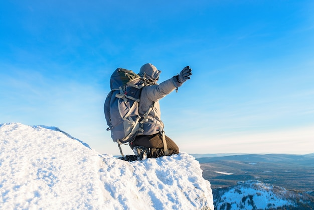 The mountaineer at the mountain top covered with ice and snow, man hiker sitting at the peak of rock and celebrates the success and amazing view from high altitude