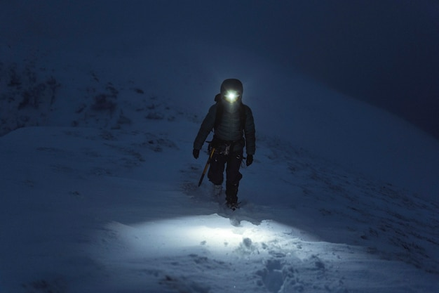 Mountaineer trekking in a cold night at liathach ridge, scotland