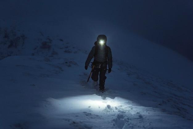 スコットランドのリアサックリッジで寒い夜にトレッキングする登山家