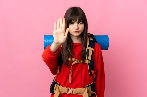 Mountaineer ukrainian girl with a big backpack isolated on pink background making stop gesture with her hand
