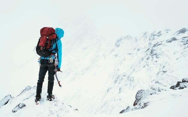 スコットランドのグレンシールにあるフォーカンリッジを登るためにピッケルを使用する登山家