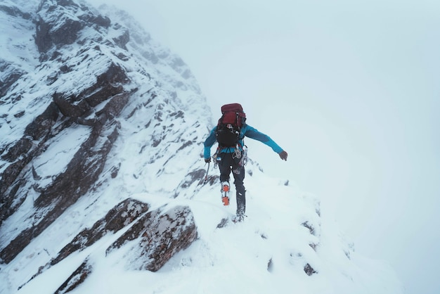 Альпинист с ледорубом для восхождения на хребет форкан в глен-шил, шотландия.
