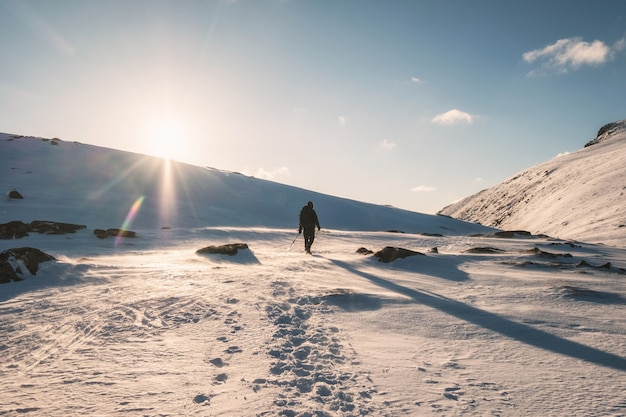 Альпинист, идущий по заснеженной горе с солнечным светом на горе райтен