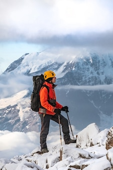 A mountaineer with a large backpack on his shoulders walks up a stone slope