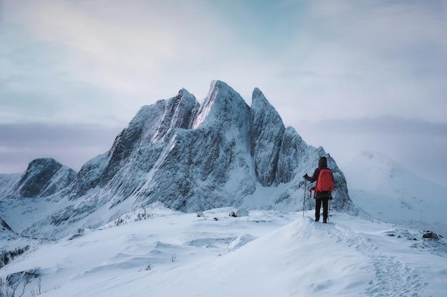 Senja 섬에서 겨울에 눈 덮인 장엄한 산 segla 피크 꼭대기에 서있는 산악인 여자