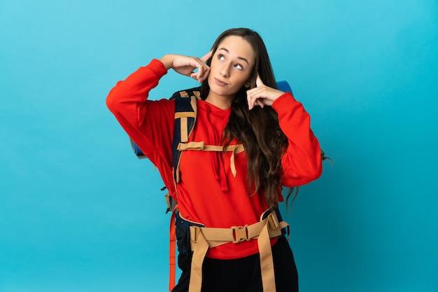 Женщина-альпинист с большим рюкзаком на изолированном фоне сомневается и думает