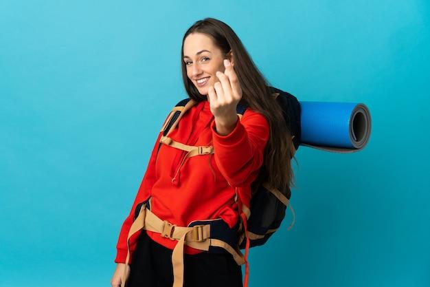 Женщина-альпинист с большим рюкзаком на изолированном фоне делает денежный жест