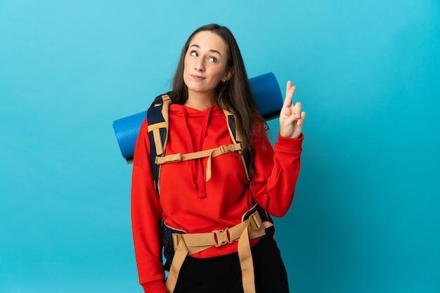 指が交差し、最高を願って孤立した背景の上に大きなバックパックを持つ登山家の女性
