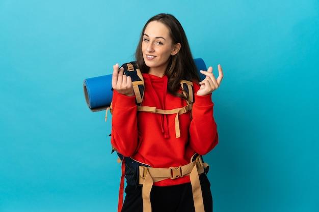 お金のジェスチャーを作る孤立した壁の上の大きなバックパックを持つ登山家の女性