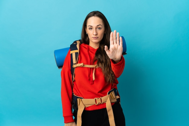 Mountaineer woman with a big backpack over isolated background making stop gesture