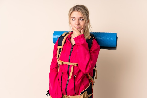 Mountaineer woman with a big backpack over isolated thinking an idea