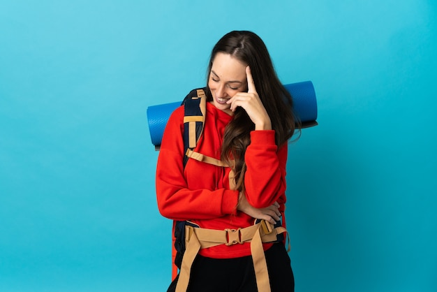 Mountaineer woman with a big backpack over isolated wall laughing