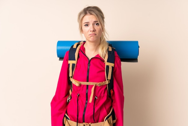 Mountaineer woman with a big backpack over isolated wall sad