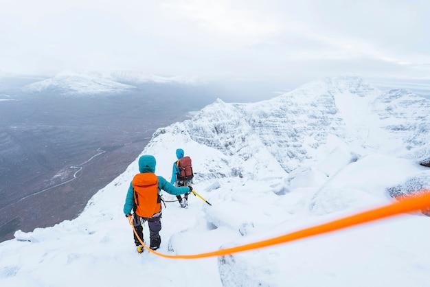 스코틀랜드의 눈 덮인 liathach 능선을 등반하는 산악인