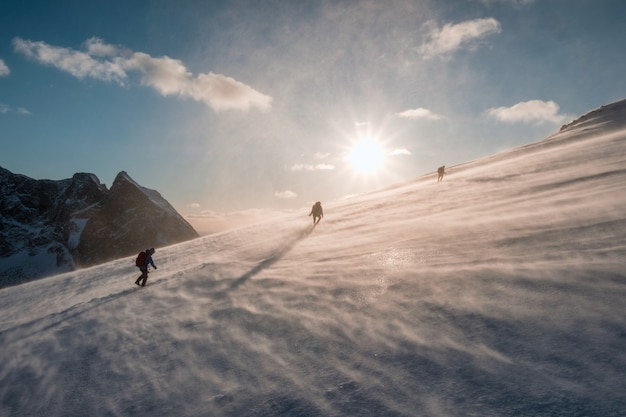 Mountaineers climbing in blizzard snowy hill at sunset