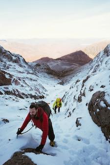 눈 덮인 산을 오르는 등산객들