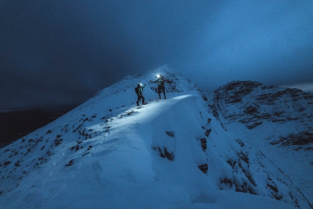 Mountaineers trekking in the cold night at liathach ridge, scotland