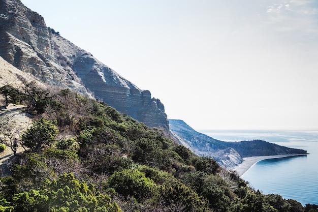 Гористый скалистый берег ранней весной, заросший можжевеловым хвойным лесом.