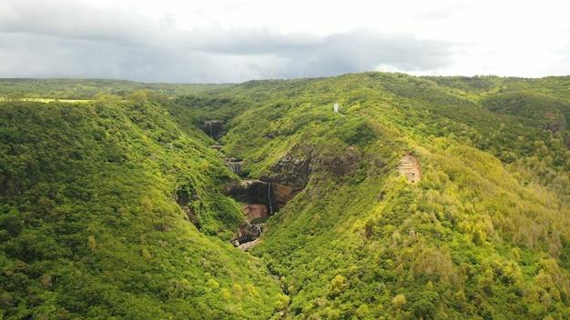 Горы и между ними водопад и озеро с высоты птичьего полета.