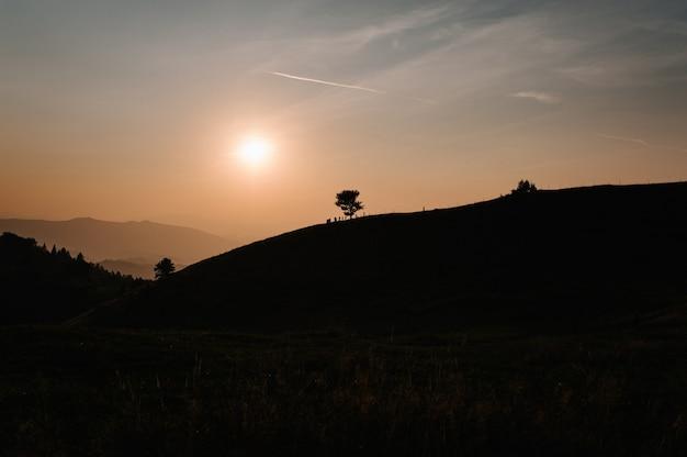 Горы и закат карпаты, украина. туманный уступ горы, красивый закат над широкой долиной. на горизонте одно дерево. линия неба самолетов.