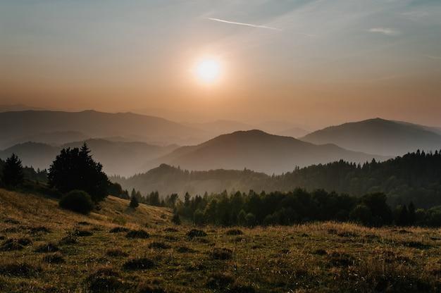 Горы и закат карпаты украина. туманный уступ горы, красивый закат над широкой долиной. на горизонте деревья. линия неба самолетов. туман в горах. солнце светит