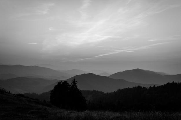 Горы и закат карпаты украина. туманный уступ горы красивый. вечер, солнце зашло над широкой долиной. на горизонте деревья. туман в горах. черно-белое фото