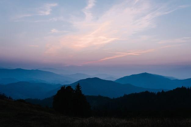 Горы и закат карпаты украина. туманный уступ горы красивый. вечер, солнце зашло над широкой долиной. на горизонте деревья. туман в горах.