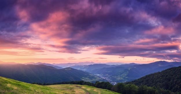 여름에 아름 다운 석양에 산입니다. 푸른 잔디가 있는 초원, 활기찬 구름이 있는 하늘, 숲이 있는 산이 있는 다채로운 탁 트인 풍경. 언덕에 흔적. 여행과 자연. 경치