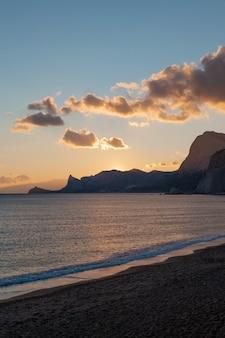 海に沈む夕日の山々