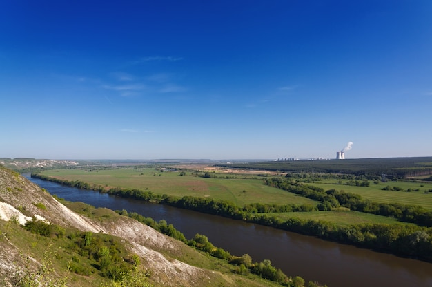 Mountains of chalk on the banks of the don river in central russia. landscape view from the hills. nuclear power station on the horizon.