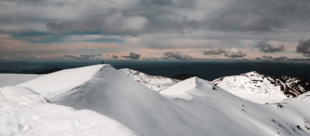 Mountains covered in snow under a cloudy sky