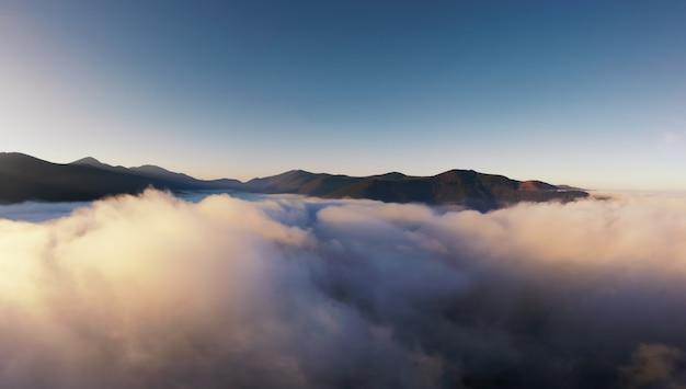 이른 아침에 안개로 뒤덮인 산. 산 꼭대기에서 새벽. 항공 사진.
