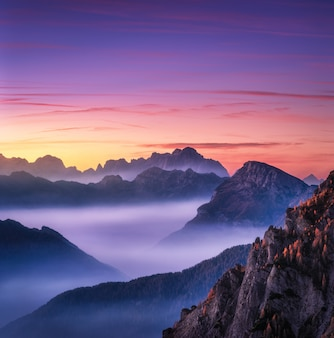 Mountains in fog at beautiful sunset in autumn in dolomites, italy.