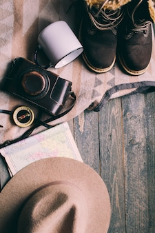 Mountains hiking stuff on wooden floor boots camera hat map compass