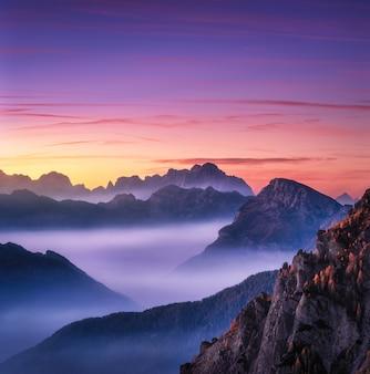 Горы в тумане на красивый заход солнца в осени в доломитах, италии.