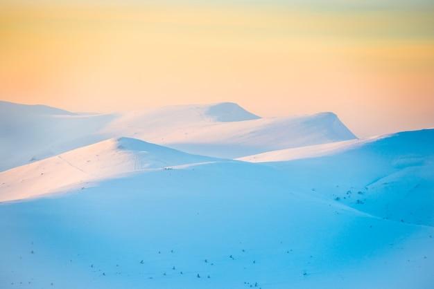 雪の山。丘に沈む夕日の風景