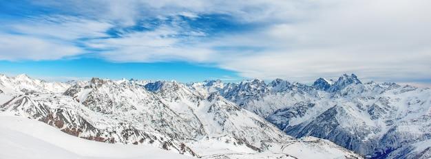 雪の山。ピークと青い空と冬の風景のパノラマ