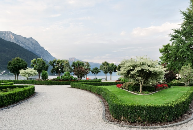 The mountains, the lake and the embankment of the city with trimmed trees, shrubs, lawn and flower beds.