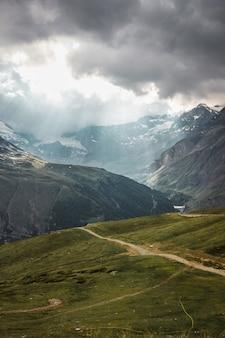 잔디와 돌이 있는 구름 경로의 마터호른 근처 산 체르마트 스위스 알프스 태양 광선