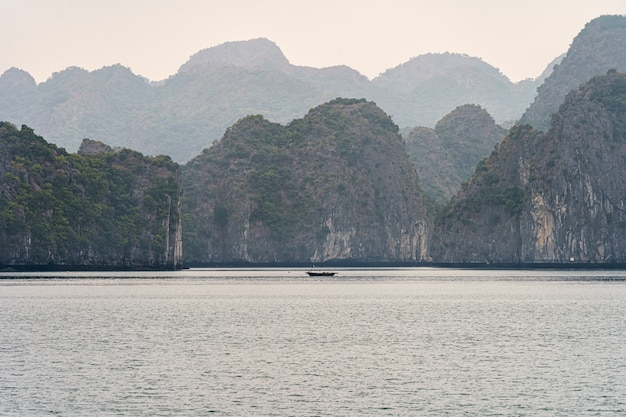 Горы бухты халонг с лодкой на воде